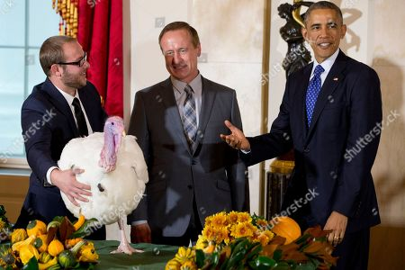 """Barack Obama, Gary Cooper, Cole Cooper President Barack Obama, right, pardons """"Cheese,"""" the turkey at the White House in Washington, during the annual Thanksgiving ceremony. Cole Cooper, far left, and his father Gary Cooper, chairman of the National Turkey Federation, helped hold """"Cheese"""" during the event"""