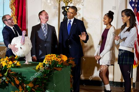 """Barack Obama, Malia Obama, Sasha Obama, Gary Cooper, Cole Cooper President Barack Obama gestures that his daughters Sasha, second from right, and Malia, right, would rather pass on touching """"Cheese,"""" the turkey during a ceremony at the White House in Washington, where the president traditionally pardons turkeys saving them from the dinner table. Standing from left are Cole Cooper and his father Gary Cooper, chairman of the National Turkey Federation"""