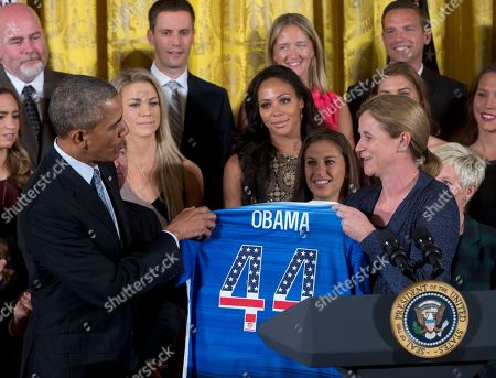 Barack Obama, Jill Ellis, Carli Lloyd, Julie Johnston, Sydney Leroux President Barack Obama receives a jersey from head coach Jill Ellis as he welcomes the U.S. Women's National Soccer Team, in the East Room of the White House in Washington, during a ceremony to honor the team and their victory in the 2015 FIFA Women's World Cup. In the background right of Obama are Julie Johnston, Sydney Leroux, and Carli Lloyd