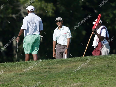Ron Kirk, Barack Obama President Barack Obama, center, speaks with Ron Kirk, left, while golfing at Vineyard Golf Club, in Edgartown, Mass., on the island of Martha's Vineyard. President Obama is taking a two-week summer vacation on the island. Golf caddy at right is unidentified
