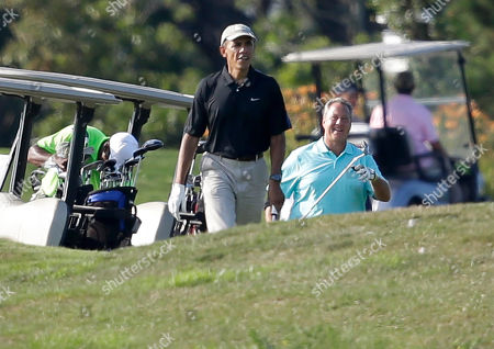 Barack Obama, Robert Wolf President Barack Obama, center, and golf partner Robert Wolf, right, walk toward a green while golfing at Farm Neck Golf Club, in Oak Bluffs, Mass., on the island of Martha's Vineyard. President Obama on Saturday left Washington for his familiar spot on Martha's Vineyard for a two-week summer vacation