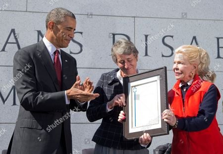 Barack Obama, Lois Pope, Sally Jewell President Barack Obama, left, is presented a plaque by philanthropist Lois Pope, right, and Secretary of the Interior Sally Jewell, during the American Veterans Disabled for Life Memorial dedication ceremony in Washington, . President Obama paid tribute to disabled U.S. veterans on Sunday, pointing to the dedication of a new memorial honoring those severely injured in war as a symbol of the nation's perseverance and character