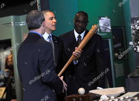 Barack Obama, Jeff Idelson, Andre Dawson President Barack Obama, accompanied by Baseball Hall of Fame President Jeff Idelson,left, and hall of fame member Andre Dawson, inducted in 2010, holds up Babe Ruth's bat during a tour the Baseball Hall of Fame in Cooperstown, N.Y., . Obama visited the museum to highlight tourism and steps to help spur international visits to the 50 states. Obama said the overall U.S. economy and local businesses will benefit if it isn't a hassle for people from other countries to visit the U.S. and spend money at its hotels, restaurants, tourist destinations and other businesses
