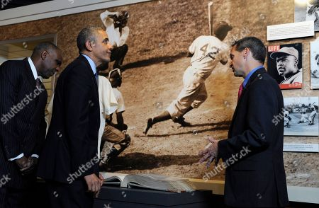 Barack Obama, Jeff Idelson, Andre Dawson President Barack Obama, accompanied by Baseball Hall of Fame President Jeff Idelson, right, and baseball hall of fame member Andre Dawson, inducted in 2010, looks over a collection item from Jackie Robinson during a tour the Baseball Hall of Fame in Cooperstown, N.Y., . Obama visited the museum to highlight tourism and steps to help spur international visits to the 50 states. Obama said the overall U.S. economy and local businesses will benefit if it isn't a hassle for people from other countries to visit the U.S. and spend money at its hotels, restaurants, tourist destinations and other businesses