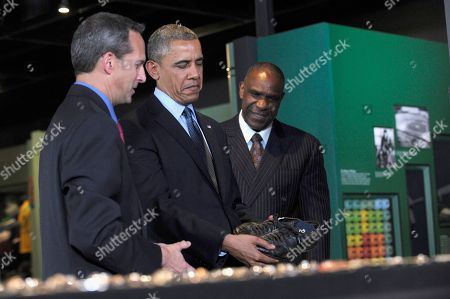 """Barack Obama, Jeff Idelson, Andre Dawson President Barack Obama, accompanied by Baseball Hall of Fame President Jeff Idelson, left, and baseball hall of fame member Andre Dawson, inducted in 2010, looks at the shoes that """"Shoeless"""" Joe Jackson, wore during a tour the Baseball Hall of Fame in Cooperstown, N.Y., . Obama visited the museum to highlight tourism and steps to help spur international visits to the 50 states. Obama said the overall U.S. economy and local businesses will benefit if it isn't a hassle for people from other countries to visit the U.S. and spend money at its hotels, restaurants, tourist destinations and other businesses"""