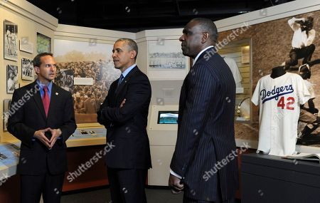Barack Obama, Jeff Idelson, Andre Dawson President Barack Obama, accompanied by Baseball Hall of Fame President Jeff Idelson, left, and baseball hall of fame member Andre Dawson, inducted in 2010, looks over a collection item from Jackie Robinson during a tour the Baseball Hall of Fame in Cooperstown, N.Y., . Obama visited the museum to highlight tourism and steps to help spur international visits to the 50 states. Obama said the overall U.S. economy and local businesses will benefit if it isn't a hassle for people from other countries to visit the U.S. and spend money at its hotels, restaurants, tourist destinations and other businesses