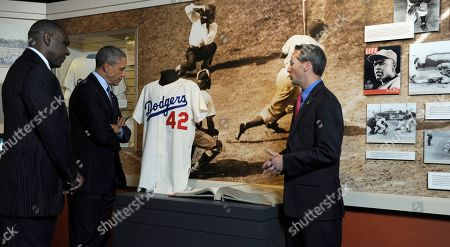 Barack Obama, Jeff Idelson, Andre Dawson President Barack Obama, accompanied by Baseball Hall of Fame President Jeff Idelson, right, and hall of fame member Andre Dawson, inducted in 2010, looks over a collection item from Jackie Robinson during a tour the Baseball Hall of Fame in Cooperstown, N.Y., . Obama visited the museum to highlight tourism and steps to help spur international visits to the 50 states. Obama said the overall U.S. economy and local businesses will benefit if it isn't a hassle for people from other countries to visit the U.S. and spend money at its hotels, restaurants, tourist destinations and other businesses