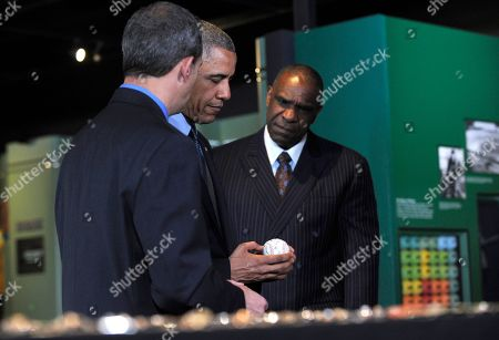 Barack Obama, Jeff Idelson, Andre Dawson President Barack Obama, accompanied by Baseball Hall of Fame President Jeff Idelson, left, and baseball hall of fame member Andre Dawson, inducted in 2010, holds a 9/11 baseball during a tour the Baseball Hall of Fame in Cooperstown, N.Y., . Obama visited the museum to highlight tourism and steps to help spur international visits to the 50 states. Obama said the overall U.S. economy and local businesses will benefit if it isn't a hassle for people from other countries to visit the U.S. and spend money at its hotels, restaurants, tourist destinations and other businesses
