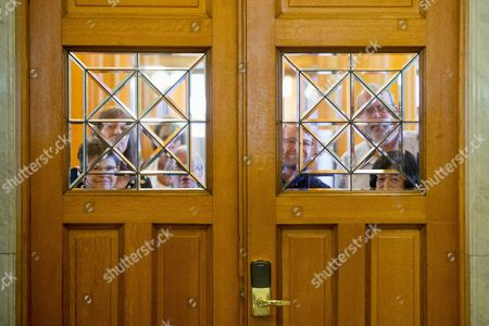 Visitors to the State Library of Iowa in the Ola Babcock Miller Building stare through windows after President Barack Obama arrives for an interview with Pulitzer Prize winning Iowa writer Marilynne Robinson, in Des Moines. While in Iowa, Obama is expected to officially announce a change to the college financial aid system