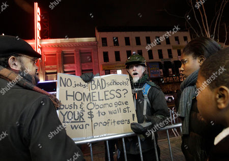 Occupy Harlem protester John McDermott, center, talks to a passerby as Assita and Hamzata Diallo listen to the conversation across the street from the Apollo Theater where President Barack Obama held one of several fundraisers he attended in New York