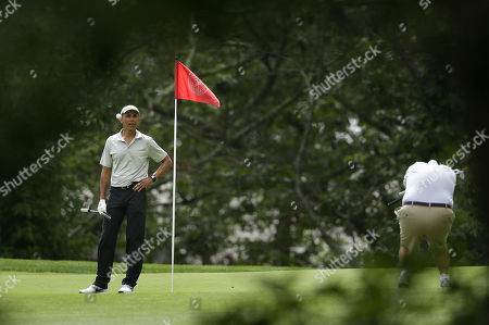 Barack Obama, Robert Wolf President Barack Obama watches as a ball arrives on the green as golfing partner Robert Wolf, right, bends to avoid the incoming ball, at Farm Neck Golf Club, in Oak Bluffs, Mass., on the island of Martha's Vineyard