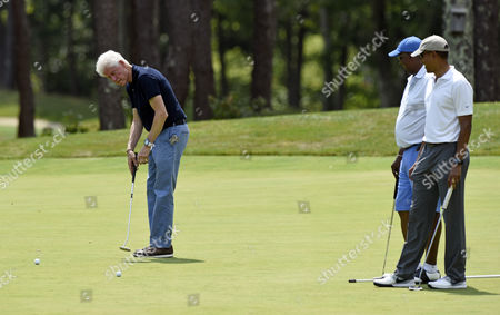 Stock Picture of Barack Obama, Ron Kirk, Bill Clinton President Barack Obama, right, and Ron Kirk, center, former United States Trade Representative, watch as former President Bill Clinton putts as they play golf on the first hole at Farm Neck Golf Club in Oak Bluffs, Mass., on Martha's Vineyard, . Obama and his family vacation every August on Martha's Vineyard, and he's been spending most of this year's two-week trip on the golf course, at the beach and dining at the island's upscale restaurants