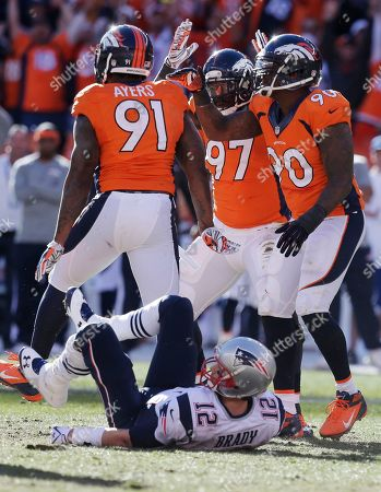 Denver Broncos defensive end Robert Ayers (91) is congratulated by his teammates Malik Jackson (97) and Shaun Phillips (90) after sacking New England Patriots quarterback Tom Brady (12) during the first half of the AFC Championship NFL playoff football game in Denver