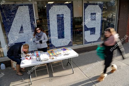 Penn State students Jackie Jones, left, of Pittsburgh, and Jacqueline Browne, center, from South River, NJ., man a bake sale table in front of the Penn State Student Bookstore in State College, Pa., . The NCAA announced a settlement Friday, with the university that will give the school back 112 wins wiped out during the Jerry Sandusky child molestation scandal and restore the former Penn State football coach Joe Paterno as the winningest coach (409) in major college football history