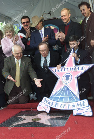 """NEALON Banjo legend Earl Scruggs, center, is presented his Walk of Fame Star, the 2,215th, by Hollywood honorary mayor Johnny Grant, left, in the Hollywood section of Los Angeles, . In the back from left are Donna Douglas and Max Baer Jr. from the """"The Beverly Hillbillies,"""" Dwight Yoakam, Henry Juszkiewicz, Gibson Guitar Corp. chairman, and Kevin Nealon. At lower right is Leron Gubler, president of the Hollywood Chamber of Commerce"""