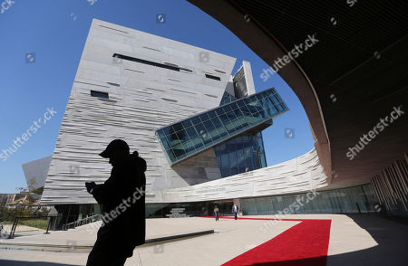 Visitors walk outside the front entrance of the of the Perot Museum of Nature and Science during a media preview in Dallas, . The museum set to open Dec. 1 was named for billionaire former presidential candidate Ross Perot and his wife, Margot, after their five children made a $50 million gift in honor of them