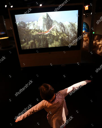 Emma Fisk Emma Fisk spreads her arms like wings rto control a virtual bird while using an interactive display that simulates bird flight at the Perot Museum of Nature and Science during a media preview in Dallas, . The museum set to open Dec. 1 was named for billionaire former presidential candidate Ross Perot and his wife, Margot, after their five children made a $50 million gift in honor of them