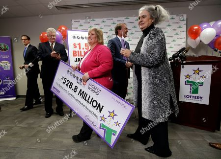 Rebecca Hargrove, Lisa Robinson Lisa Robinson, center, carries a ceremonial check as she leaves a news conference with Rebecca Hargrove, right, president and CEO of the Tennessee Lottery, in Nashville, Tenn. The Robinsons' winning Powerball ticket is one of three winning tickets in the $1.6 billion jackpot drawing held Wednesday