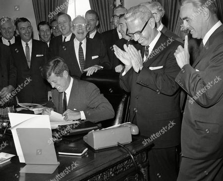 """Stock Photo of John Kennedy, JFK Laughter marks a White House bill-signing ceremony in Washington on . As President John F. Kennedy thanked Congress members who helped pass legislation for training of unemployed workers, Rep. Carroll Kearns (R-Pa.), quipped """"Even the Republicans?"""" Standing, from left: Sen. Maurice Murphy (R-N.H.); Rep. Charles Joolson (D-N.J.); James Sundquist, assistant to Sen. Joseph Clark (D-Pa.); Rep. Charles Goodell (R-N.Y.); Kearns; Rep Peter Garland (R-Me.); George Meeny, almost hidden, AFL-CIO president; Rep. Elmor Holland (D-Pa.); Sen. Jennings Randolph (D-W.Va.); Labor Secretary Arthur Goldberg and, in rear, Sen. Pat McNamara (D-Mich"""