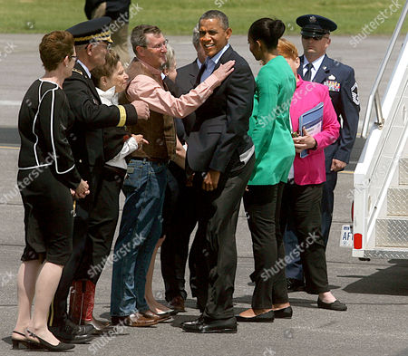 U.S. President Barack Obama, with First Lady Michelle Obama, right, greet former U.S. Senator Kent Conrad and other dignitaries in Bismarck, N.D. after arriving on Air Force One
