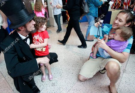Presidential presenter Robert Broski as Abraham Lincoln is photographed with Chloe, 3, by her father Walter O'Brien and her sister Maggie, from Yorba Linda during the President's Day celebration at The Richard Nixon Presidential Library and Museum on in Yorba Linda, Calif