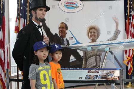 Robert Broski, as Abraham Lincoln, is photographed with Sally Choe, 11, and Mathew Choe, 9, from South Korea during a visit on President's Day at The Richard Nixon Presidential Library and Museum on in Yorba Linda, Calif