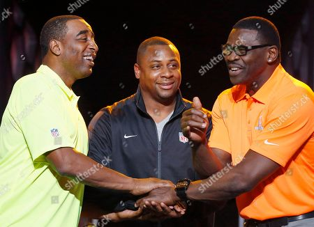 Cris Carter, Michael Irvin, Troy Vincent Troy Vincent, center, NFL Executive Vice President of Football Operations, smiles as he watches Michael Irvin, right, NFL Hall of Fame member and Pro Bowl Alumni captain, and Cris Carter, left, NFL Hall of Fame member and Pro Bowl Alumni captain, laugh as they battle for the coin toss on who gets to pick the first player during the Pro Bowl Kickoff news conference, in Phoenix. The upcoming NFL Pro Bowl football game will be played on Sunday