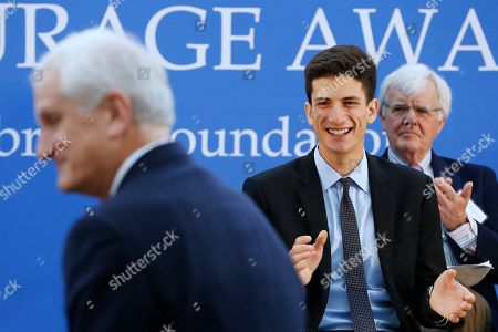 Edwin Schlossberg, Jack Schlossberg, Albert Hunt Jack Schlossberg, center, applauds as his father Edwin Schlossberg, left, is introduced during the John F. Kennedy Profile in Courage Award ceremony at the John F. Kennedy Presidential Library in Boston, . Jack Schlossberg presented the award to Connecticut Gov. Dannel P. Malloy for his vocal support of refugee resettlement. Chairman of the John F. Kennedy Profile in Courage Award Committee, Albert Hunt, is at right