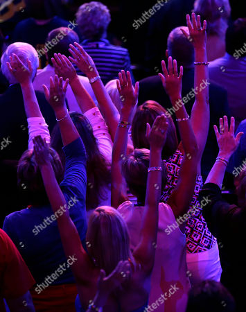 Delegates sway their arms back and forth to the music of Neal Boyd during the Republican National Convention in Tampa, Fla., on