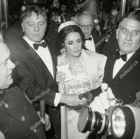 """Columbia pictures Vice President Robert Ferguson, right, holds tight to Richard Burton's hand and helps guide him and Elizabeth Taylor through mob on at premiere of """"Dr. Faustus,"""" at Cinema 57 in New York City on . Other persons in the photo are unidentified. The crowd was so thick the Burtons took nearly ten minutes to move, with the aid of police from the curb to inside the theater"""