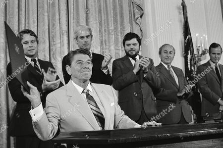 President Ronald Reagan holds up the Captive Nations Week Proclamation, after signing it during a ceremony at the White House, Washington, D.C. Applauding the President from left are, Rep. Christopher Smith, R-N.J.; Rep. John Edward Porter, R-Ill.; and Kenneth Tomlinson, head of Voice of America. Man second from right is unidentified. Vice president George H.W. Bush is at right