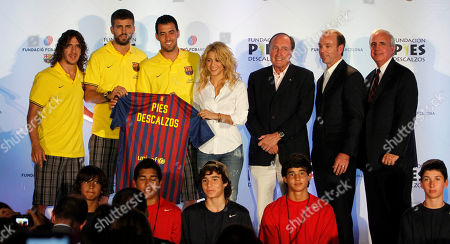 Stock Photo of Carlos Pujol, Gerard Pique, Sergio Busquets, Shakira, Ramon Pont, Brian Mormile, Carlos Gimenez From left, FC Barcelona soccer players Carlos Pujol, Gerard Pique, Sergio Busquets, Colombian pop star Shakira, Ramon Pont, Vice president of FCBarcelona, Brian Mormile, Chairman, Board of Directors - YMCA of Greater Miami, and Carlos Gimenez, Miami-Dade County Mayor, pose for photos in Coral Gables, Fla., . Shakira announced an initiative between her Barefoot Foundation, or Pies Descalzos, and the Foundation FC Barcelona that includes the construction of sport and recreation facilities in the Colombian city of Cartagena, as well as in Miami