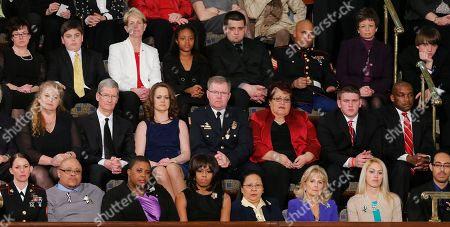 First lady Michelle Obama, front row, center, and other, listen as President Barack Obama gives his State of the Union address during a joint session of Congress on Capitol Hill in Washington, . Front row, from left are, Sgt. Sheena Adams, Nathanial Pendleton, Cleopatra Cowley-Pendleton, Mrs. Obama, Menchu Sanchez, Jill Biden, Kaitlin Roif and Alan Aleman.Second row, from from left are, Deb Carey, Apple CEO Tim Cook, Amanda McMillan, Lt. Brian Murphy, Marie Lopez Rogers and Bradley Henning. Third row, third from left are,Tracey Hepner, Haile Thomas, Lee Maxwell, Sgt. Carlos Evand and White House seniot adviser Valerie Jarrett