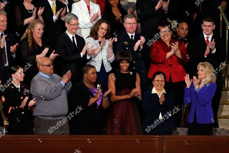 First lady Michelle Obama is applauded before President Barack Obama's State of the Union address during a joint session of Congress on Capitol Hill in Washington, . Front row from left are Sgt. Sheena Adams, Nathaniel Pendleton, Cleopatra Cowley-Pendelton, Obama, Menchu Sanchez and Jill Biden. Second row from left are Oregon Gov. John Kitzhaber, Deb Carey, Tim Cook, Amanda McMillan, Lt. Brian Murphy, Marie Lopez Rogers, and Bradley Henning