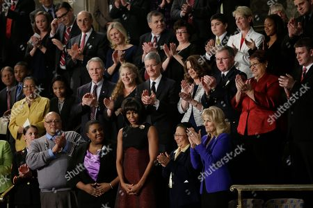 First lady Michelle Obama is applauded before President Barck Obama's State of the Union address during a joint session of Congress on Capitol Hill in Washington, . Front row, from left are, Sgt. Sheena Adms, Nathaniel Pendleton, Cleopatra Cowley-Pendleton, Mrs, Obama, Menchu de Luna Sanchez and Jill Biden. Second row, third from left are, Oregon Gov. John Kitzhaber, Deb Carey and Apple CEO Tim Cook Amanda McMillian, Lt. Brian Murphy