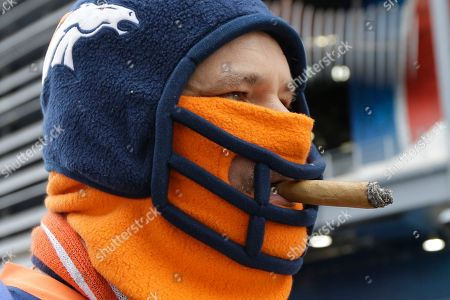Denver Broncos fan Steve Richards of Minneapolis smokes a cigar before the NFL Super Bowl XLVIII football game, in East Rutherford, N.J