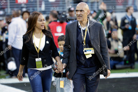Former NFL football player and head coach Tony Dungy, right, walks with his wife Lauren Harris Dungy before the NFL Super Bowl 50 football game between the Denver Broncos and the Carolina Panthers, in Santa Clara, Calif