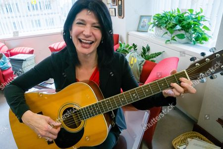 """Lily Eskelsen Garcia National Education Association (NEA) President Lily Eskelsen Garcia poses with her guitar after an interview with The Associated Press in her office at NEA headquarters in Washington. Garcia is a Spanish speaking, guitar playing author and a former Utah teacher of the year who doesn't shy from criticizing what she describes as """"toxic"""" testing"""