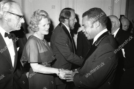 British Conservative Party Leader Margaret Thatcher shakes hands with Newark Mayor Kenneth Gibson at a reception, in New York. Leonard M. Greene, President of the Institute for Socio-Economic Studies is at center and Denis Thatcher, Mrs. Thatcher's husband is at far left