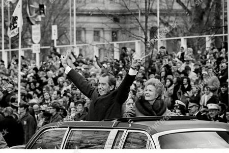 """Richard Nixon, Patricia Nixon U.S. President Richard Nixon extends his arms and fingers in a """"V"""" sign as is wife Pat smiles at his side in limousine taking them along the inaugural parade route in Washington, D.C"""