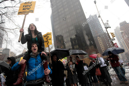 Hannah Russell-Goodson, top, of Boston, and Julian Brand, bottom, of Portland, Maine, chant slogans during a demonstration against Egyptian President Hosni Mubarak near the United Nations headquarters, in New York