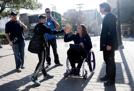 Amy Van Dyken, Jesse Stephans, Lydia Stephan, Tom Rouen Former Olympic swimmer Amy Van Dyken, center, gets a high five from Jesse Stephans, 12, son of Pac-12 Networks president Lydia Stephans, at right, as Van Dyken's husband Tom Rouen, in blue, looks, in Berkeley, Calif. The six-time Olympic gold medal swimmer returned to work with the Pac-12 Networks on Friday, nearly eight months after an all-terrain vehicle accident left her paralyzed from the waist down
