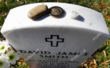 A coin from Vice President Joe Biden sits on top of the tomb of US Marine Sgt. David James Smith, after he visited Section 60, on Veterans' Day, at Arlington National Cemetery in Arlington, Va