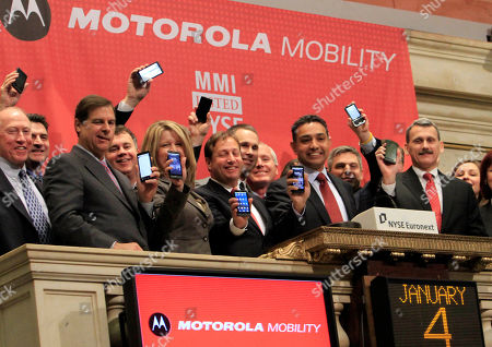 Marc Rothman, Dan Moloney, Evan Solomon Motorola Mobility executives Marc Rothman, center, senior vice president and CFO, Sanjay Jha, second from right, chairman and CEO, and Dan Moloney, right, president, hold up their mobile devices as they prepare to ring the opening bell at the New York Stock Exchange