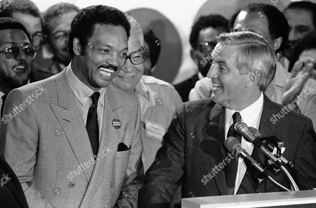 Presidential candidate Walter Mondale and Jesse Jackson have big smiles for each other at night, in St. Paul, at a press conference to announce Jackson's support of the Mondale-Ferraro ticket. Behind them is Mayor Coleman Young of Detroit