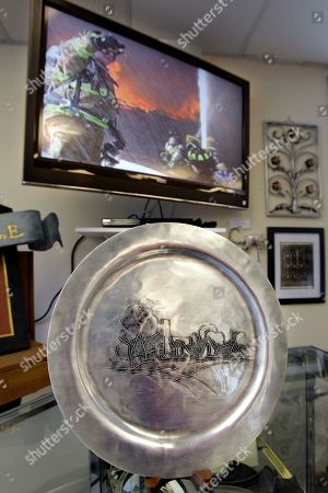 Stock Photo of Taken at the Wendell August Forge temporary museum and gift shop in Grove City, Pa., a plate made for Edgar J. Kauffman, the owner of the historic Pittsburgh department store, is displayed in front of a video showing firefighters battling the March 2010 fire that destroyed the factory of the Wendell August Forge. Six months after that fire destroyed their buildings on March 6, company president Will Knecht says his community, employees and customers have rallied to re-energize his 87-year-old handcrafted metal business, about 45 miles north of Pittsburgh