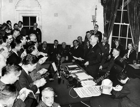 President Harry S. Truman smiles happily as he announces to the press the complete victory of the Allies over Germany, during a ceremony at the White House in Washington, D.C., . Seated near the wall behind Truman are, left to right: Elmer Davis, Secretary Henry A. Wallace, Maj. Gen. Philip Fleming, Rep. Joseph Martin, Jr., Gen. George C. Marshall, J. Leonard Reinsch, Col. Harry Vaughan, John Snyder, first lady Bess Truman, Mary Margaret Truman and Secretary of War Henry Stimson. Fred M. Vinson is in the foreground