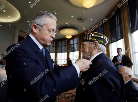 Guy Wildenstein,William Spriggs Guy Wildenstein, president of the American Society of the French Legion of Honor, left, presents an the legion's insignia to World War II veteran William Spriggs of Massena, N.Y., during a ceremony at the U.S. Military Academy, in West Point, N.Y. Thirty-four veterans were honored 70 years after of the D-Day landings
