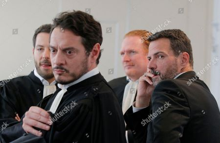 Former trader Jerome Kerviel, right, his lawyers Benoit Pruvost, 2nd right, David Koubbi, 2nd left, and a unidentified one wait in the Versailles appeal court, west of Paris, . A French court has cut the civil damages owed by former trader Jerome Kerviel from 4.9 billion euros ($5.5 billion) to 1 million euros ($1.1 million