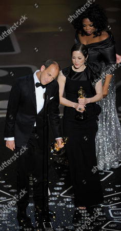 """Charles Ferguson and Audrey Marrs accept the Oscar for best documentary feature for """"Inside Job"""" at the 83rd Academy Awards, in the Hollywood section of Los Angeles"""